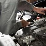 Male hand repairing car engine...