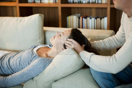 Photo for Young woman receiving head massage at home - Royalty Free Image