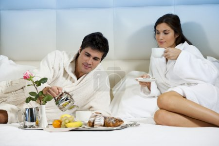 Photo for Relaxed Couple in Bed, hotel room - Royalty Free Image