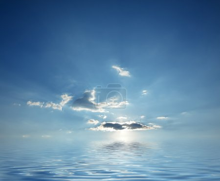 Blue cloudy sky sunrise over calm ocean water
