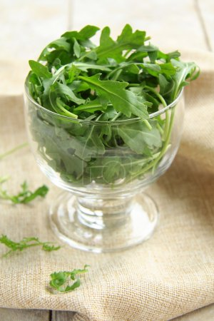 Photo for Fresh green Arugula salad on wooden table - Royalty Free Image