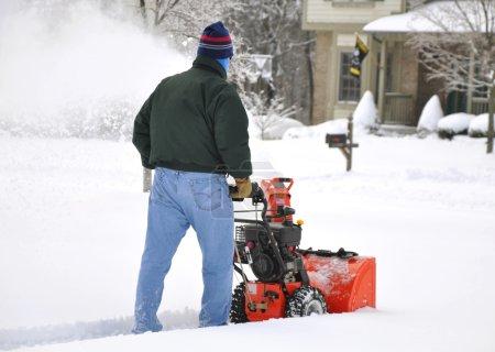Photo pour Homme utilisant une souffleuse à neige après une forte chute de neige - image libre de droit