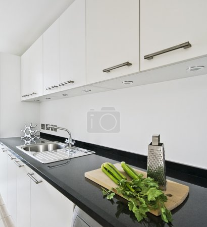 Photo for Contemporary white kitchen with black granite worktop - Royalty Free Image