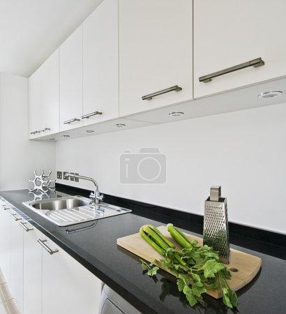 Foto de Cocina blanca contemporánea con encimera de granito negro - Imagen libre de derechos