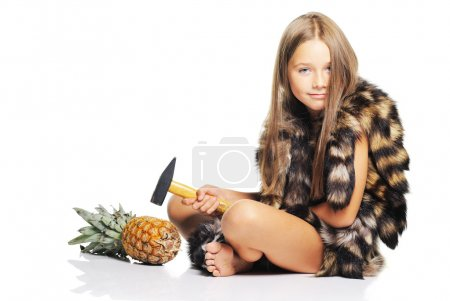 Little girl with big pineapple and hammer