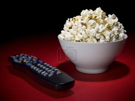 Photo pour Un bol de pop-corn et d'une télécommande, prête pour le plaisir. - image libre de droit