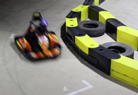 Photo for Auro racing track with one motion blurred go-cart - Royalty Free Image
