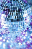 Shiny disco ball in blue light