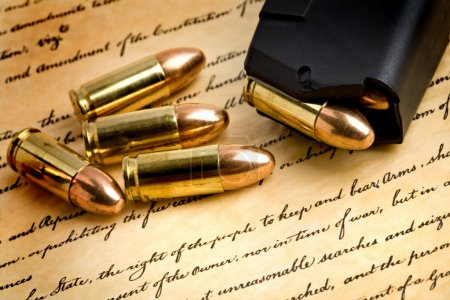 Photo for Bullets and modern loaded 9mm clip over the bill of rights, focus on the right of the to keep and bear arms - Royalty Free Image