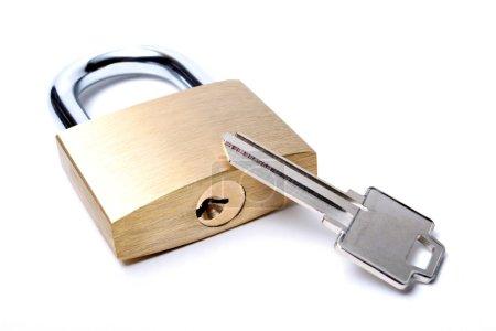 Photo pour Serrure avec une clé non coupée. macro sur blanc avec une profondeur de champ limitée . - image libre de droit