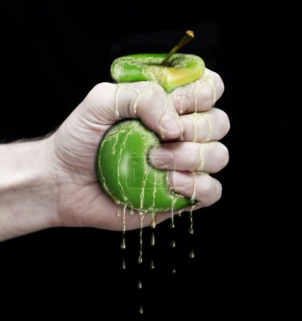 Photo for Hand to squeeze an green apple - Royalty Free Image