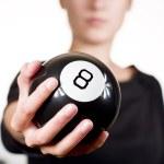 Woman holding black 8 ball (pool)...