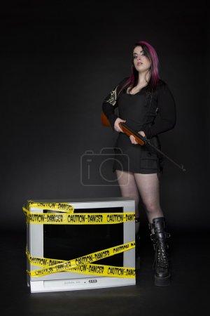 Photo pour Femme tenant un fusil debout à côté d'une télévision avec un robinet de danger jaune dessus - image libre de droit